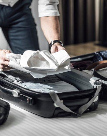 Anzug in den Koffer packen